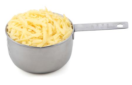 queso rallado: Queso rallado en una taza de medir de América, aislado en un fondo blanco