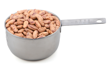 Borlotti beans also known as cranberry beans, roman or romano beans, in an American measuring cup, isolated on a white background Archivio Fotografico