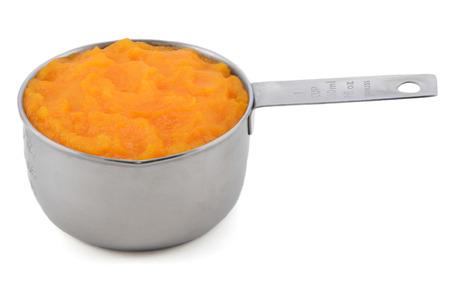 calabaza: Pur� de calabaza en una taza de medir de Am�rica, aislado en un fondo blanco