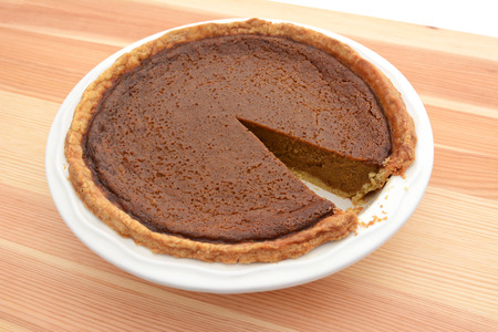 are taken: Slice taken from a freshly baked pumpkin pie in a dish Stock Photo