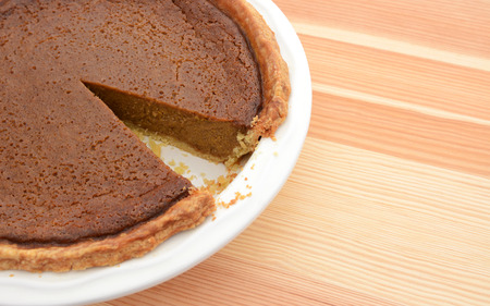 are taken: Close-up of cut pumpkin pie with a slice taken, on a wooden table Stock Photo