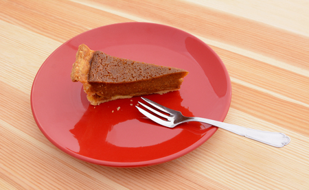 dessert fork: Slice of pumpkin pie with a dessert fork on a red plate on a wooden kitchen table