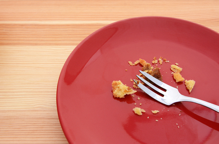 eaten: Crumbs remain from an eaten slice of pumpkin pie, with a fork on a red plate