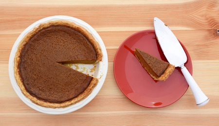 are taken: Slice taken from a pumpkin pie with a pie server on a red plate Stock Photo