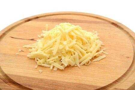 grated cheese: Queso rallado sobre una tabla de cortar de madera Foto de archivo
