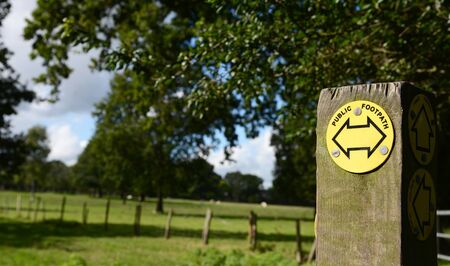 fencepost: Public footpath sign on a post points left and right in the countryside. Lush fields and trees beyond.
