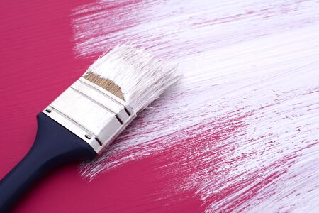 previously: Dirty paintbrush with white paint rests on half-painted board, previously painted pink