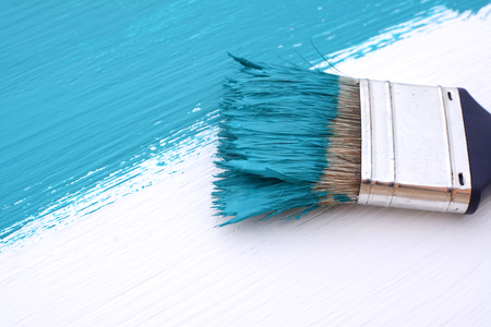 bristle: Close-up of paintbrush with paint-covered bristles painting a white board blue Stock Photo