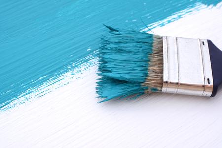 brocha de pintura: Primer plano de la brocha con cerdas cubiertas de pintura que pinta un tablero blanco azul Foto de archivo