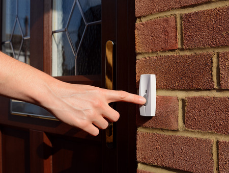 Woman extends her hand to ring a doorbell at the front door of a house