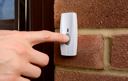 hand bell: Close-up of woman pressing the button of a doorbell on a brick wall Stock Photo