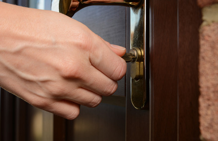 abrir puertas: Mujer gira la llave en una cerradura en una puerta exterior