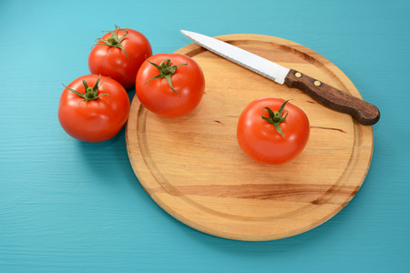 serrated: Fresh tomatoes with a serrated kitchen knife on a wooden chopping board