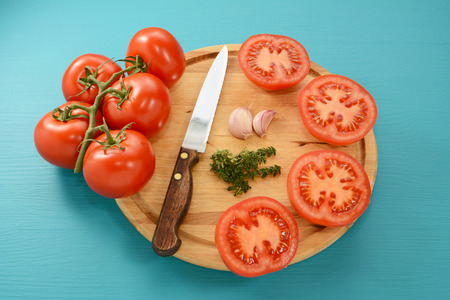 serrated: Tomatoes cut for roasting with serrated knife and garlic and thyme on wooden board