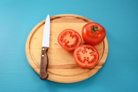 serrated: Whole and halved red tomato with serrated kitchen knife on a wooden chopping board