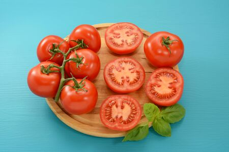 halved  half: Tomatoes - cut, whole and on the vine with a sprig of fresh basil on a wooden board