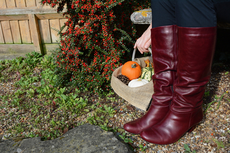 knee boots: Woman in burgundy knee high boots sits on a bench, her hand resting on a basket of pumpkins