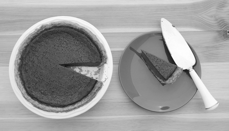 are taken: Slice taken from a pumpkin pie with a pie server on a plate - monochrome processing