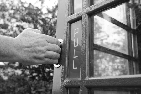 telephone box: Mans hand pulling open the door of an old-fashioned British telephone box - monochrome processing