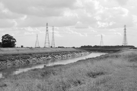 foul: Overhead power lines span the River Nene at Foul Anchor, Cambridgeshire, carrying electricity from Sutton Bridge power station. Monochrome processing Stock Photo