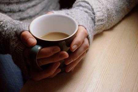 tazza di th�: La donna tiene calda tazza di t� o caff�, scaldandosi le mani, seduto a un tavolo di legno sotto luce artificiale