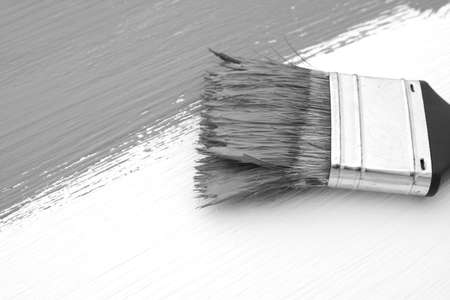 bristles: Close-up of paintbrush with paint-covered bristles painting a board - monochrome processing