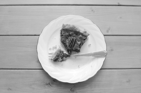 dessert fork: Half-eaten slice of pecan pie on a china plate with a dessert fork - monochrome processing