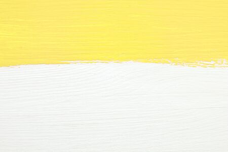 contrast: Horizontal stripe of yellow paint over white painted wooden background