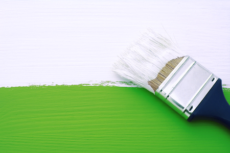 lineas horizontales: Painting green wooden surface with white paint, dirty paintbrush lies on top