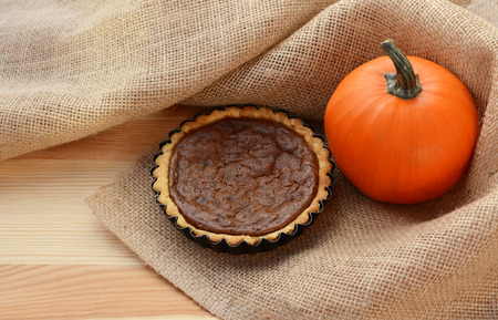 nestled: Pumpkin pie and autumnal pumpkin nestled in hessian fabric on a wooden table