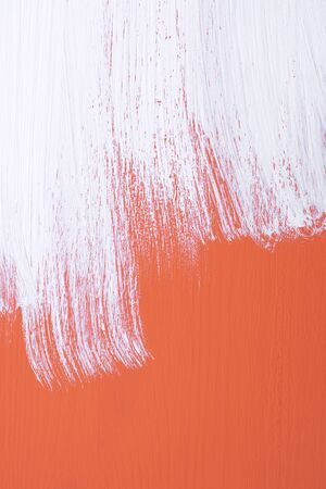 emulsion: Orange wooden board being roughly painted with a coat of white emulsion paint