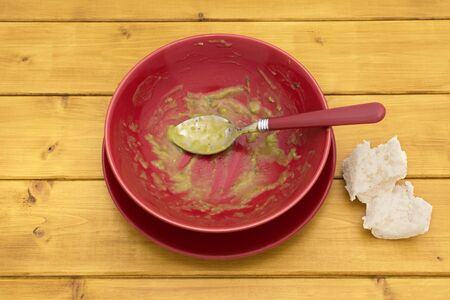 emptied: Pieces of white bread on table next to an emptied bowl of pea and ham soup Stock Photo