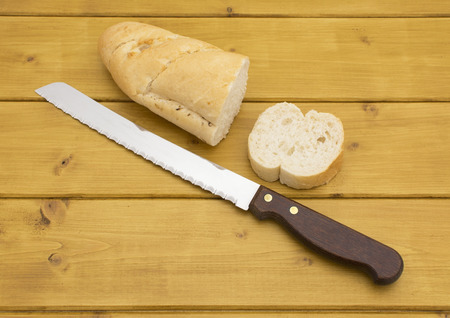 bread knife: Portion of baguette with a slice cut off, bread knife beside on wooden table