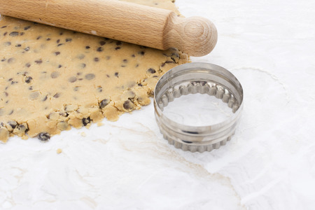 biscuit dough: Circular cookie cutter with chocolate chip biscuit dough and wooden rolling pin Stock Photo