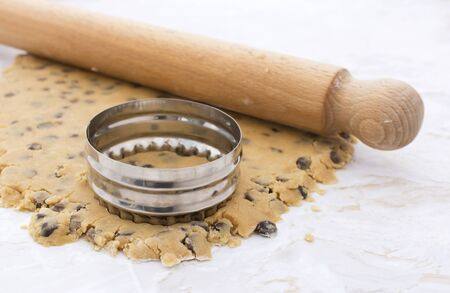 Cookie cutter and wooden rolling pin on rolled out peanut butter and chocolate chip cookie dough Stock Photo