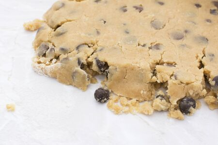 biscuit dough: Close-up of crumbly chocolate chip cookie dough rolled out on a kitchen worktop Stock Photo