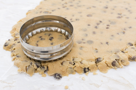 kitchen worktop: Detail of metal cookie cutter cutting circle from chocolate chip cookie dough on a kitchen worktop Stock Photo