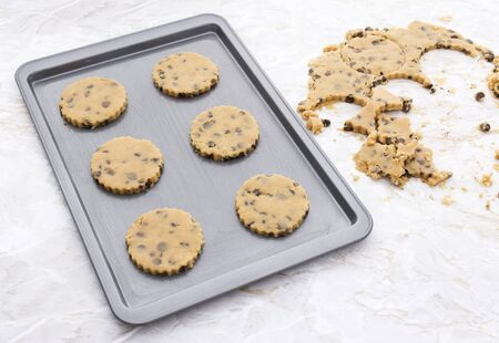 baking tray: Six chocolate chip cookies on a metal baking tray, raw cookie dough scraps on kitchen table Stock Photo