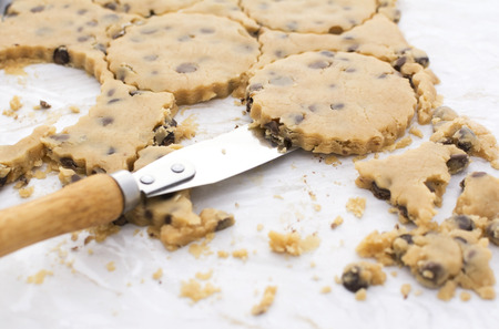 palette knife: Close-up of palette knife lifting peanut butter and chocolate chip cookies from kitchen worktop
