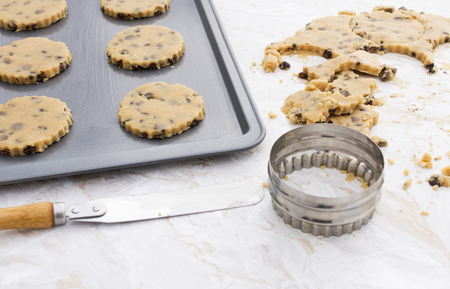 palette knife: Making chocolate chip cookies - circles of dough on baking tray, palette knife and cookie cutter on worktop Stock Photo
