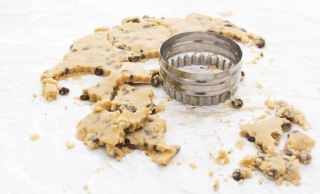 cookie cutter: Circular cookie cutter with scraps of chocolate chip biscuit dough on a kitchen work surface Stock Photo