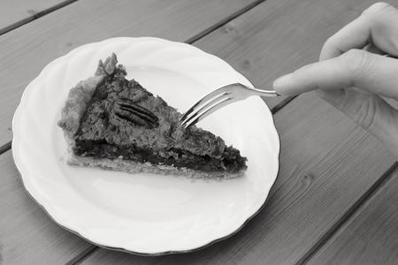pecan pie: Young woman using a dessert fork to cut into a portion of pecan pie - monochrome processing Foto de archivo