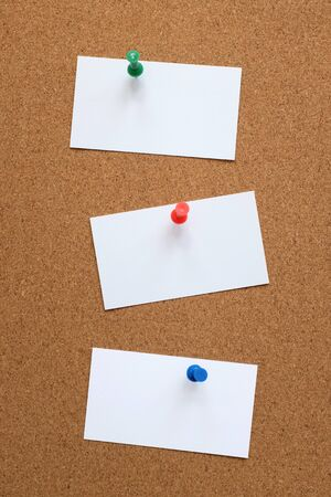 pin board: Three blank business cards pinned to a cork pin board