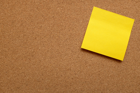 pin board: Yellow sticky note stuck on corner of cork pin board with copy space Stock Photo