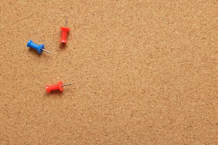 drawing pins: Three drawing pins on an empty cork noticeboard with copy space