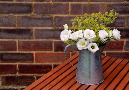 alchemilla mollis: White prairie gentian flowers with ladys mantle in a metal pitcher on a wooden table against a brick wall with copy space