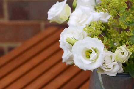 alchemilla: Close-up of white tulip gentian blooms with ladys mantle on a wooden slatted table