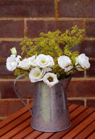 alchemilla mollis: Floral arrangement of white prairie gentians and delicate alchemilla mollis in a vintage metal jug on a wooden table against a brick wall