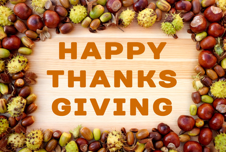 horse chestnuts: HAPPY THANKSGIVING greeting written on wooden background with beechnuts, horse chestnuts and acorns frame