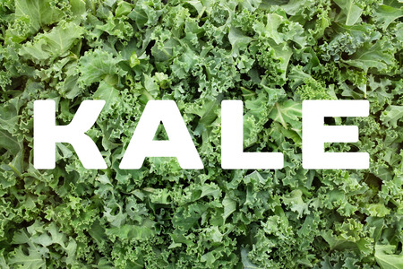 cruciferous: KALE text written over green chopped kale leaves background